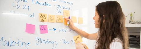 woman writing notes on a white board