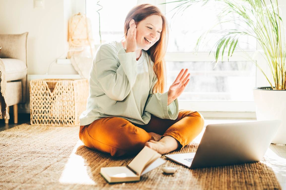 Woman smiling at home during a virtual meeting | What is Ableism? Confronting Ableism in the Workplace