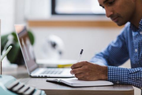 Person writing in notebook while working at computer